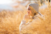 Woman sitting in tall grass in autumn — Stock Photo