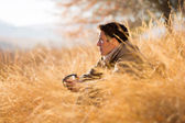 Man sitting in tall grass in autumn — Stock Photo