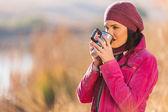 Girl drinking coffee outdoors in autumn — Stock Photo