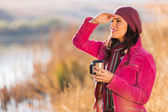 Woman holding coffee mug outdoors in winter — Stock Photo