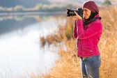 Photographer take photos outdoors in autumn — Stock Photo
