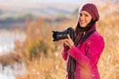 Young woman holding a dslr camera — Stock Photo
