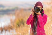 Young woman photographing in autumn — Stock Photo