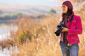 Young female photographer holding camera outdoors — Stock Photo