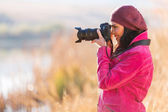 Female photographer taking photos — Stock Photo
