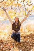 Young woman throws autumn leaves — Stock Photo