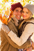 Young couple hugging in autumn forest — Stock Photo