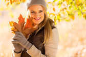 Woman holding bunch of autumn leaves — Stock Photo