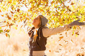 Autumn leaves falling on happy young woman — Stock Photo