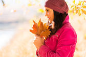 Side view of young woman holding autumn leaves — Stock Photo