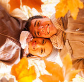 Underneath view of young couple holding autumn leaves — Stockfoto