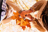 Couple holding autumn leaves — Stock Photo