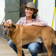Cowgirl and her dog inside farm house — Stock Photo #50635879