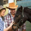 Cowboy and cowgirl comforting a horse in stable — Stockfoto