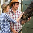 Cowboy and cowgirl in stable touching a horse — Stockfoto