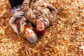 Young couple lying on autumn leaves — Stock Photo