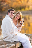 Couple wrapped in blanket and enjoying wine at sunset — 图库照片