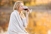 Blond woman drinking red wine at sunset — Stock Photo