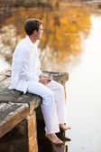 Young man sitting on wooden pier by the lake — Stock Photo