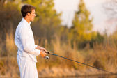 Young man holding fishing rod — Stock Photo