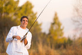 Young man catching a fish with rod — Stock Photo