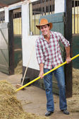 Cowboy working in stable — Stock Photo
