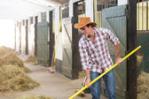 Cowboy working in a stable — Stock Photo