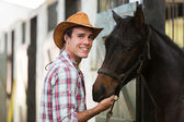 Cowboy with a horse in stable — Stock Photo