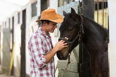 Horse breeder comforting a horse — Stock Photo