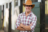 Cowboy with arms crossed in stable — Stock Photo