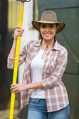 Female farmer holding a pitch fork — Stockfoto