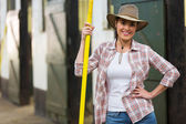 Pretty cowgirl holding pitch fork — Stockfoto