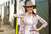 Beautiful cowgirl inside stables — Stock Photo
