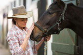 Cowgirl talking to a horse — Stock Photo