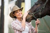 Happy cowgirl and her horse in stable — Stock Photo