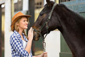 Cowgirl and horse inside stable — Stock Photo