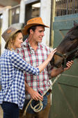 Cowboy and cowgirl in stable touching a horse — Stock Photo