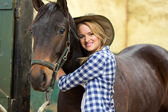 Cowgirl hugging her horse — Stock Photo