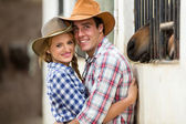 Western couple hugging in stables — Stok fotoğraf