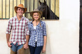 Cowboy and cowgirl couple holding hands — Stock Photo