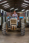 Cowboy driving tractor inside stables — Stock Photo