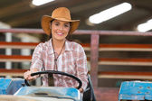 Female farmer driving a tractor — Stockfoto