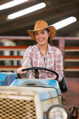 Cowgirl driving tractor — Photo
