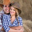 Young farming couple hugging in barn — Stock Photo #50641325
