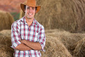 Cowboy standing against hay bales — Stock Photo