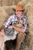 Cowboy with his dog sitting on hay — Stock Photo