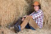 American western cowboy sitting on hay — Stock Photo
