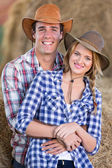 Young farming couple inside barn — Stockfoto