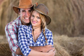 Young farming couple hugging in barn — Stock Photo