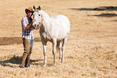 Cowboy with a white horse — Stock Photo